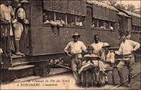 Chemin de Fer du Nord à Bonaberi. – La ligne reliant Douala à Nkongsamba est construite entre 1908 et 1911, à l'époque coloniale allemande. On l'appelle alors la « ligne du Nord », bien que ses 172 km de long ne la mènent en réalité pas bien loin dans la partie septentrionale du pays. Le projet initial était, il est vrai, de rallier  N'Gaoundéré et Garoua. De fait, la ligne devint par la suite le « chemin de fer de l'ouest », ce qui est plus conforme à son tracé. Bien plus tard, entre 1964 et 1974, un tronçon joignant Yaoundé à N'Gaoundéré devait effectivement desservir le nord du Cameroun. Equipé d'une voie unique à écartement métrique, le chemin de fer « du nord » devenu « de l'ouest » part, côté capitale économique, depuis le quartier de Bonabéri, sur la rive ouest du Wouri. Pour l'emprunter, les habitants de la ville devaient traverser le fleuve par voie navigable jusqu'à la construction du pont en 1954. – « Je quitte Douala un matin, à l'aube. Michel est venu me chercher au Gouvernement, m'a emmené au port ; nous sommes montés dans une petite vedette à pétrole, nous avons passé le Wouri. Nous sommes arrivés à un endroit qui s'appelle Bonabéri. Là, il y a une gare et un petit train. […] je suis monté dans le train ; le train est parti. On m'a donné un wagon, tout un wagon. Il y a une plateforme à l'arrière du wagon et le wagon est le dernier du train. J'ai pris un fauteuil dans le salon, je me suis assis sur la plateforme et je regarde la petite voie filer dans la forêt des deux côtés. » (1). Sources : (1) Martet, Jean, Les bâtisseurs de royaumes, Paris, Albin Michel, 1934.