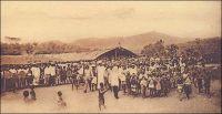 Cameroun français, en brousse, arrivée triomphale du Missionnaire au village. – « [Le Cameroun compte] en tout, une soixantaine de pères et 2500 catéchistes pour 232 000 catholiques, 142 000 catéchumènes ou 374 000 Noirs plus ou moins christianisés, soit en moyenne, un prêtre pour 6500 fidèles ou demi-fidèles et un catéchiste pour 150. […] Dans la brousse, on n'est à son presbytère que la moitié du temps. Ainsi, à Edéa, le supérieur peut en quinze jours visiter vingt-cinq de ses cinquante postes ; au sud et au sud-est, les derniers sont à cinquante ou soixante kilomètres ; faute de bonnes routes, il doit aller entièrement à pied ; il fait chaque jour plus de cinq lieues dans la région du sud où les villages sont rares, deux heures seulement de marche au sud-est où les habitations sont plus rapprochées. […] Suivant l'état des chemins, tantôt dans une vieille petite Ford, tantôt en motocyclette, tantôt à cheval, tantôt à pied, par des pistes souvent barrées de troncs d'arbres, coupées de ruisseaux, même de rivières, où il arrive qu'on trouve un vieux pont de liane qu'il faut réparer avant de s'y hasarder. ». – Carte postale éditée par la « Mission des Prêtres du Sacré-Cœur de St-Quentin ».   Source : J. Wilbois Le Cameroun, éditions Payot, Paris, 1934.