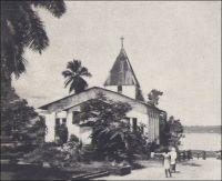 Akwa, le temple de Saker restauré, tel qu'il a subsisté jusqu'en 1945. – Le missionnaire baptiste britannique Alfred Saker est un pionnier à plusieurs titres : il fut l'un des tout premiers religieux à investir la côte que l'on nommait alors Cameroons, où il s'installa dès 1845, et il fut le premier à fabriquer des briques en terre cuite dans toute la région. En habile artisan, ce mécanicien-constructeur de marine parvint, à partir de 1860, à produire deux mille briques par semaine. Avec ce nouveau matériau, il put bâtir son temple, une école et une maison d'habitation. Ses constructions, sans briller par leur architecture, se démarquaient de l'existant où dominaient les matériaux d'origine végétale.  Le plateau d'Akwa, qui est aujourd'hui un quartier de Douala, est décrit en 1826 par un voyageur britannique comme propre, ordonné et structuré par deux vastes avenues parallèles, et surplombé par la vaste demeure à étage du roi. Quand Saker s'y installe, les rares autres constructions européennes sont des factoreries, dépôts fonctionnels destinés au commerce de traite. Il faut noter que les bâtiments érigés par Saker devaient s'avérer bien plus résistant que les premières constructions allemandes, souvent préfabriquées en bois et métal.
