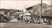 Nkongsamba, route de Bafang, années 1950. - La ville s'est développée avec l'arrivée du chemin de fer, construit entre 1907 et 1912 par les Allemands qui donnèrent alors le nom Nsamba à la localité. La ligne, appelée CFN pour chemin de fer du nord, reliait l'intérieur du pays à la côte, allant de Nkongsamba à Bonabéri, juste à coté de Douala, et passant par Mbanga avec un embranchement sur Kumba. Le chemin de fer, en ouvrant un débouché sur la côte aux productions agricoles de l'Ouest, du Sud-ouest et de la région du Moungo, scelle la prospérité de la ville. De nombreux commerçants européens, allemands, anglais, français et méditerranéens s'y établissent. Les grands comptoirs coloniaux, et tout ce qui compte dans le commerce de l'époque, y installent des succursales ; SCOA, RW King, Tsekenis, CFAO, SHO, Compagnie soudanaise, Olympius, Panafric, les établissements Mercier, John Holt, Paterson Zochonis… La ville est dotée de services officiels, et devient un centre administratif en 1923, succédant dans ce rôle à la localité de Baré. - Le tronçon de chemin de fer reliant Douala à Yaoundé, long de 262 km, fut construit entre 1908 et 1927. Il fut ensuite enrichi d'une bretelle de 30 km reliant Ngoumou à Mbalmayo, construite entre 1927 et 1933. Le tronçon allant vers le nord du pays, entre Yaoundé et Ngaoundéré, (long de 622 km) fut construit bien plus tardivement, entre 1964 et 1974.