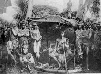 Cameroun français, un Chef en tenue de gala avec son fon masqué. Carte éditée par la mission des prêtres du Sacré-cœur de St-Quentin. - Sur cette photo, probablement prise dans les années 1920-1930, on voit un grand chef (fo) Bamiléké de l'Ouest-Cameroun, revêtu de ses vêtements d'apparat en tissu ndop (batik de coton, teint à l'indigo) et notamment sa grande coiffe de plumes (ten), son baudrier, et son immense pipe
