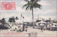 Grand Bassam, Marché et Station des bateaux de la Lagune. – Situé à l'interface entre l'océan et la lagune Ebrié, un des cordons côtiers qui longent une bonne partie du littoral, le site s'impose naturellement comme capitale dès la création de la colonie de Côte d'Ivoire en 1893. Il permet en effet d'organiser à la fois les échanges maritimes vers l'extérieur du continent et les communications vers l'intérieur du pays. Un réseau lagunaire et fluvial relie les principales agglomérations du sud du pays et les cours d'eau servant à l'époque de voie de communication vers le nord, faute de pistes. Au départ, les transbordements depuis ou vers les navires en mer sont assez périlleux. La côte d'Afrique de l'Ouest est en effet exposée à un système de vagues et de courants très violents, appelé « la barre ». Des piroguiers audacieux se sont spécialisés dans son franchissement, mais l'opération reste risquée pour les marchandises comme pour les passagers. A la toute fin du XIXe siècle, Grand-Bassam est dotée d'un wharf, sorte de ponton érigé de la plage vers l'océan, permettant de charger et décharger les navires de l'autre au-delà de la barre. Malgré ses atouts et ses équipements, le développement de la ville est stoppé par une épidémie de fièvre jaune meurtrière en 1899 – 45 des 60 Européens résidents y laissent la vie – et la capitale est transférée dans une localité située de l'autre côté de la lagune, baptisée Bingerville - en hommage au premier gouverneur de la colonie de Côte d'Ivoire, Louis-Gustave Binger. Ce cliché fait partie de l'important fond constitué par le photographe dakarois Edmond Fortier. Il se rendit en Côte d'Ivoire en 1908, accompagnant le voyage officiel du ministre des colonies du premier gouvernement Clémenceau, Raphaël Milliès-Lacroix.