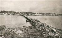Abidjan, pont de Treichville. - Cet ouvrage un peu primitif - un pont flottant -, édifié en 1931, occupait approximativement l'emplacement de l'actuel pont Houphouët Boigny. Franchissant la lagune Ebrié, il reliait le quartier du Plateau, au nord, au quartier de Treichville au sud. Il fut détruit en 1957, pour céder la place au nouveau pont. Celui-ci, construit en béton précontraint sur des pieux profonds, comporte 8 travées pour une portée totale de 372 mètres. A la fin des années 1960, un autre pont, nommé pont Charles De Gaule fut édifié selon les mêmes techniques, à quelques centaines de mètres à l'est du pont Houphouët-Boigny, pour absorber une partie du trafic automobile en plein essor. Ce nouvel édifice, long de 592 mètres, est d'ailleurs dévolu à l'usage routier. Aujourd'hui, on annonce la construction prochaine d'un troisième pont sur la lagune Ebrié. Le nouvel ouvrage, qui portera le nom de l'actuel président de la république ivoirienne – au pouvoir depuis 2000 et maintenu dans ses fonctions par des accords internationaux en attendant que la situation militaire et politique permette l'organisation de nouvelles élections présidentielles –, reliera le quartier de Yopougon à l'île Boulay. Jusqu'à présent isolée, celle-ci constitue une vaste étendue proche du centre ville, disponible pour l'extension. Elle devrait accueillir de nouvelles infrastructures portuaires, une zone franche industrielle et commerciale, et un quartier d'affaires. Trois consortiums, un français, un italien et un allemand, sont en lice pour obtenir le chantier de ce pont.