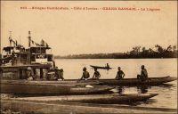 Grand-Bassam, la lagune. –  Le réseau des lagunes, fleuves et rivières du sud de la Côte d'Ivoire constitue un moyen de déplacement ancestralement utilisé. En effet, dans cette région, l'impénétrable forêt tropicale handicape le développement des transports terrestres et le phénomène de « barre » - des vagues quasi infranchissables le long du littoral – y rend le cabotage maritime périlleux. A côté des innombrables pirogues indigènes qui assurent le trafic local, le colonisateur met en place rapidement une flotte motorisée pour acheminer marchandises et passagers. L'irrégularité des chenaux navigables – en largeur et en profondeur – et les difficultés de la navigation pendant les basses eaux impose l'emploi d'un matériel fluvial peu encombrant. Un système de  petits remorqueurs, tractant des barges de 50 tonnes, est adopté. Ces remorqueurs à fond plat, d'une vingtaine de mètres de long, ont un tirant d'eau d'un mètre à 1,5 mètre. Ils sont mus par deux machines à vapeur de 40 à 50 CV chacune, fonctionnant au bois de chauffage et prélevant leur eau dans la lagune. Un seul bateau porteur circulait dans le premier tiers du XXème sièlce, le Plajodel, en service entre Bassam et Assigny. Ses dimensions l'empêchaient  d'ailleurs d'emprunter le canal menant à la lagune de Lahou.