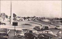Abidjan, vue du pont de la poste. – Il s'agit en fait d'une vue de la place Lapalud, aux extrémités opposées de laquelle se trouvent effectivement la Poste et  le pont Houphouët-Boigny. Construite en 1957, cette place est inaugurée le 15 mars 1958 en même temps que le pont qu'elle prolonge. En forme d'hémicycle, elle constitue la pointe sud de la presqu'île lagunaire du Plateau. Elle porte en son centre un monument emblématique, constitué d'une colonne verticale en dessous de laquelle se trouve la statue d'une femme portant sur sa tête un panier rempli de feuilles. La légende veut qu'une femme rencontrée un jour en ce lieu soit à l'origine du nom de l'actuelle capitale économique de la Côte d'Ivoire. Ainsi, au XVIIIème siècle, des français, venus reconnaître l'endroit, croisèrent là une femme rentrant de la cueillette. Tandis qu'ils lui demandaient d'où elle venait, elle répondit « t'chan m'bi djan », ce qui signifie « j'étais allé couper des feuilles » en Ebrié. Transcrit phonétiquement, ce que les explorateurs avaient pris pour le nom du lieu, devait rester. La place, qui portait le nom de Maurice-Pierre Lapalud, gouverneur de la Côte d'Ivoire entre 1925 et 1930, fut rebaptisée en 1961 place de la République.