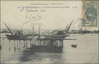 Grand-Bassam, le wharf, vue prise de la rade. – « Nous passons devant Grand-Lahoue : quelques factoreries établies entre la lagune et la mer. Grand-Bassam a cependant un wharf, qui permet de débarquer en évitant la barre ; on nous l'ouvre par faveur, car il n'est pas encore « reçu » par le service des Travaux publics (le lecteur voudra bien se souvenir que nous sommes en 1900) » (1). –  Ce premier wharf, long de 177 m, est inauguré en 1901. En 1923 l'adjonction, toujours à Grand-Bassam, d'un nouveau wharf de 288 m, permet d'accroître de 140 000 t. la capacité annuelle du trafic maritime. En 1931, , un nouveau wharf situé à Port-Bouët est mis en service pour décongestionner les installations de Grand-Bassam. Plus proche d'Abidjan, celui-ci est supposé inciter les entreprises à se rapprocher de la capitale, dans laquelle le percement d'un canal entre océan et lagune doit permettre d'installer un port eau profonde. Le projet, qui remonte au début du XXème siècle et avait été abandonné au moment de la première guerre mondiale, voit finalement le jour avec l'ouverture du canal de Vridi en 1951, scellant l'abandon des wharfs. Source : (1) Gouraud, Gal, Zinder Tchad, Paris, Plon, 1944.