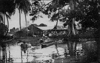 Débarcadère d'une factorerie de lagune. – Le commerce de traite, qui prévaut dans le système colonial, consiste à échanger des marchandises manufacturées occidentales contre des matières premières tropicales, lesquelles sont ensuite revendues sur le marché métropolitain. Selon les époques et les lieux, ces échanges utilisent la monnaie, ou s'en affranchissent. La factorerie est la base locale de ce négoce. La première factorerie de Côte d'Ivoire aurait été créée en 1863 par le rochelais Arthur Verdier, à Assinie, où résidait alors le représentant de la France. Le peu d'empressement des grandes compagnies commerciales à développer leur réseau en Côte d'Ivoire, laissa la place à de petits commerçants qui maillèrent progressivement le territoire. A partir de 1858, les négociants étrangers furent d'ailleurs autorisés à s'installer dans les comptoirs français. La factorerie à proprement parler (on ne voit ici que le débarcadère) n'est bâtie en dur que lorsqu'elle s'est avérée viable commercialement, disposant d'un réseau de sous-factoreries dans l'intérieur du pays. La construction comprend alors un solide rez-de-chaussée, pour protéger le stock, aux épais murs de maçonnerie de pierre ou de briques importées, et avec de petites ouvertures à barreaux. L'habitation du traitant est aménagée à l'étage, dans un bâti plus léger, et entourée d'une galerie.
