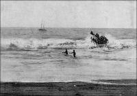 Grand-Bassam, le surf-boat a bondi au sommet de la barre. – Le débarquement acrobatique sur les côtes du golf de Guinée tel qu'il avait lieu avant la construction des wharfs. Le voilier que l'on aperçoit au second plan de l'image, est une  goélette qui servait de « salle d'attente » aux voyageurs arrivant. Déposés là par les paquebots, ils pouvaient avoir à passer plusieurs jours à bord, avant que ne se présente le moment propice pour franchir la barre. Le wharf de Grand-Bassam fut construit en 1897. La photo et le récit qui suit sont donc antérieurs. « Il y a trois jours, le paquebot venant de Marseille mouillait devant Grand-Bassam ; je m'imaginais être au terme de mes tribulations sur mer, je m'apprêtais à débarquer… une surprise m'attendait. D'un ton légèrement narquois le commandant du bord m'annonça que la barre était infranchissable… Jusqu'ici ne n'avais vu de barre qu'à l'embouchure des rivières. Dans le golfe de Guinée le phénomène se produit sur toute la côte et est dû à une disposition particulière du littoral. […] Ici la pente de la plage est très rapide : les lames qui s'y précipitent rencontrent presque un à-pic, et leur pied heurtent un obstacle, elles s'écoulent sur elles-mêmes, sapées dans leur base, cataractes et tourbillons qui écrasent sous leur masse et rejettent brisées à terre les barques assez téméraires pour vouloir passer. C'est la barre. […] Seul un wharf pourrait dompter les flots et s'avancer, victorieux, au-devant des paquebots ; mais à Grand-Bassam le wharf est encore à l'état de projet. Que deviennent les donc les passagers lorsque la barre est impraticable et que nulle embarcation n'ose l'affronter ? L'administration, toujours prévoyante, a résolu ce problème : en rade se balance une vieille goélette solidement ancrée au milieu des vagues, sorte de ponton qui assure un asile aux voyageurs en détresse. Trois matelots nègres et un patron également noir ont la garde du bord.» témoignage rapporté par le colonel Baratier (1). Source (1) B