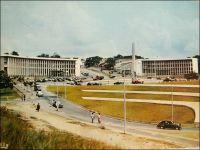 Abidjan, la Place Lapalud. – Construite en 1957, elle est inaugurée le 15 mars 1958 en même temps que le pont Houphouët Boigny qu'elle prolonge.  En forme d'hémicycle, elle constitue la pointe sud de la presqu'île lagunaire du Plateau. Elle porte en son centre un monument emblématique, constitué d'une colonne verticale en dessous de laquelle se trouve la statue d'une femme portant sur sa tête un panier rempli de feuilles. La légende veut qu'une femme rencontrée un jour en ce lieu soit à l'origine du nom de l'actuelle capitale économique de la Côte d'Ivoire. Ainsi, au XVIIIème  siècle, des français, venus reconnaître l'endroit, croisèrent là une femme rentrant de la cueillette. Tandis qu'ils lui demandaient d'où elle venait, elle répondit « t'chan m'bi djan », ce qui signifie « j'étais allé couper des feuilles » en Ebrié. Transcrit phonétiquement, ce que les explorateurs avaient pris pour le nom du lieu, devait rester. La place, qui portait le nom de Maurice-Pierre Lapalud, gouverneur de la Côte d'Ivoire entre 1925 et 1930, fut rebaptisée en 1961 place de la République. Le boulevard Antonétti, du nom du gouverneur colonial de 1918 à 1924, et que l'on voit sur cette photo monter vers l'intérieur du Plateau entre les bâtiments de la Poste et de la direction des douanes, devait quant à lui devenir boulevard de la République.