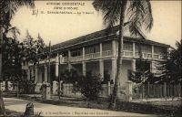 Grand-Bassam, le Tribunal. – Ce bâtiment fut construit en 1911, alors que la capitale de la colonie de Côte d'Ivoire avait déjà quitté Grand Bassam pour être transférée à Bingerville, suite aux épidémies de fièvre jaune qui avaient décimé la population de la ville côtière en 1863, 1898 et 1899. Il abritait le tribunal de première instance, et resta un haut lieu de justice jusqu'à ce qu'il soit remplacé, en 1954, par le palais de justice d'Abidjan flambant neuf. – « Le Parquet, le Tribunal, ainsi que les Câbles sous-marins, sont toujours installés à Bassam ». Source : Guid'AOF, Dakar, édition 1948.
