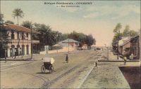 Conakry, Rue Commerciale - Également connue comme rue, avenue ou boulevard du Commerce ou encore « 3ème boulevard », cette artère majeure de la capitale guinéenne aboutit au port. En 1899, l'administrateur Bie la décrit en ces termes : « n'a pas moins de 30 m. de large sur une longueur d'environ un kilomètre. De larges trottoirs bordant cette rue, de splendides maison à étage, toutes neuves, lui donnent une apparence toute moderne » (1). Le chemin de fer Decauville, que l'on distingue sur l'image, fut déployé dans ce quartier de négoce à partir de 1897. Cette installation, constituée de rails écartés de 60 cm et fixés sur des traverses métalliques, était souvent désignée comme « petite vitesse », par opposition au chemin de fer plus rapide et en voies métriques qui joignait le fleuve Niger. A partir de 1902, elle totalisait 9,7 kilomètres de voies. Son usage n'était pas réservé au commerce, et les particuliers pouvaient y faire circuler des marchandises, moyennant un droit de 1 franc par tonne transportée et en fournissant le véhicule et son mode de traction. Les wagonnets de promenade, emportant des passagers, n'étaient pas soumis à cette taxe. Source (1) : Bie. A. (administrateur), Voyage à la côte occidentale d'Afrique, de Marseille à Conakry, Conakry le 20 mai 1899 (archive privée citée par Odile Goerg dans Rives Coloniales, Soulilou, Jacques, éditeur scientifique, Paris, édition Parenthèses et édition Orstom, 1993).