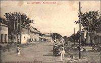 Conakry, rue commerciale. - Connue également comme avenue commerciale, rue, avenue ou boulevard du Commerce ou encore « 3ème boulevard », cette artère majeure de la capitale guinéenne aboutit au port. L'administrateur Bie la décrit ainsi en 1899 : « n'a pas moins de 30 m. de large sur une longueur d'environ un kilomètre. De larges trottoirs bordant cette rue, de splendides maison à étage, toutes neuves, lui donnent une apparence toute moderne » (1). Le chemin de fer Decauville, que l'on distingue sur l'image, fut déployé dans ce quartier de négoce à partir de 1897. Cette installation, constituée de rails écartés de 60 cm et fixés sur des traverses métalliques, était souvent désignée comme « petite vitesse », par opposition au chemin de fer plus rapide et en voies métriques qui joignait le fleuve Niger. A partir de 1902, elle totalisait 9,7 kilomètres de voies. Son usage n'était pas réservé au commerce, et les particuliers pouvaient y faire circuler des marchandises, moyennant un droit de 1 franc par tonne transportée et en fournissant le véhicule et son mode de traction. Les wagonnets de promenade, emportant des passagers, n'étaient pas soumis à cette taxe. Source (1) : Bie. A. (administrateur), Voyage à la côte occidentale d'Afrique, de Marseille à Conakry, Conakry le 20 mai 1899 (archive privée citée par Odile Goerg dans Rives Coloniales, Soulilou, Jacques, éditeur scientifique, Paris, édition Parenthèses et édition Orstom, 1993).