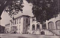 Conakry, le palais du gouverneur. – Bâti entre fin 1889 et mi 1890, cet hôtel cossu devait en imposer : « Les indigènes sentiront l'autorité et la respecteront davantage en voyant une construction plus grandiose et plus en harmonie avec le grade du haut-fonctionnaire qui l'habitera », écrivait le conducteur des travaux dans un rapport, juste avant le début du chantier (1). Il est vrai que le premier résident à avoir représenté la France sur place, le Dr Péreton, arrivé en 1885, avait été bien mal loti. Faute de résidence, il était resté longtemps l'hôte de la maison de commerce SCOA, dans des conditions très précaires. De fait, le palais fut construit massif : 21 X 17 m. pour une hauteur de plus de 15 m., avant même l'ajout dès 1892 de deux ailes.  De plus, il bénéficiait d'un confort sophistiqué, notamment grâce à des circulations d'air, ménagées dans le soubassement, protégées par des grilles en fontes, et dans les combles. Premier grand édifice érigé à Conakry, il devait rester le siège du gouverneur de la colonie, jusqu'à l'indépendance, le 2 octobre 1958. Et il n'échappa pas aux conditions tendues du divorce entre Paris et la Guinée : « Les Français en partant ont détruit les archives, ils ont tout emporté. Le palais du gouverneur, qui sera plus tard la résidence du chef de l'Etat, a été vidé de tout son contenu. La vaisselle qu'ils n'ont pas pu emporter, ils l'ont brisée [...] et nous avons débuté avec nos affaires personnelles » expliquait récemment Andrée Sékou Touré, la femme du premier président de la Guinée indépendante (2). Le palais, que l'on assimilait désormais à la funeste mémoire de ce dernier occupant, fut rasé l'année même de sa disparition en 1984. Le nouveau palais présidentiel, construit pour son successeur, devait à son tour être détruit par des tirs d'artillerie lors d'une mutinerie de l'armée, en 2005. Sources : (1) cité par Odile Goerg, dans Soulilou, J. (éditeur scientifique), Rives coloniale, Paris, éditions Parenthèses et éditions de l'O