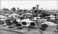 Conakry, vue panoramique au tout début du XXème siècle. – Le développement des centres guinéens se fit au gré des cycles commerciaux successifs, caractérisés par la domination d'un produit d'exportation : esclaves, arachide, caoutchouc, banane et enfin bauxite. L'édification de Conakry fut portée par le cycle du caoutchouc. L'emplacement, choisi pour résidence du commandant du cercle de Dubrékà en 1885, puis chef-lieu des Rivières du Sud et enfin capitale de la Guinée Française en 1893, avait été retenu pour son vide politique et commercial. Cette création ex nihilo permit aux administrateurs et ingénieurs de Travaux Publics de donner libre cours à leurs projets d'urbanisme. Le résultat, mêlant homogénéité des constructions et maîtrise de la végétation, fut si réussi qu'il valut pendant longtemps à la ville le surnom de « perle de la côte occidentale d'Afrique ». Source : Goerg, Odile, La Guinée Conakry dans Rives Coloniales, Paris, éditions Parenthèses et éditions de l'Orstom, 1993.