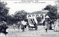 Une noce à la Côte. Le coupé des mariés. – La Guinée maritime était occupée, encore au XIXème siècle, par des populations peu évoluées et peu islamisées. L'influence économique et sociale du commerce maritime européen, remontant pourtant au XVème siècle, était restreinte à quelques clans privilégiés qui contrôlaient les comptoirs et leurs abords. Longtemps, ces derniers contribuèrent au désordre persistant dans la région, en se livrant à de perpétuelles rivalités armées, souvent suscitées par les commerçants européens concurrents. Cette insécurité persistante n'étant pas favorable au commerce conventionnel, c'est principalement la traite d'esclaves qui se développa. Si une grande partie de la population des « Rivières » restait en marge de ce commerce, il émergea néanmoins au XIXème siècle une bourgeoisie fortunée de commerçants et de planteurs esclavagistes, mêlant les descendants métis de traitants américains, portugais ou français à des éléments de la chefferie locale, et vivant matériellement à l'européenne. L'implantation de sociétés commerciales européennes dès le début du XXème siècle, favorisée par l'administration coloniale, devait disqualifier cette élite économique locale, la ramenant au rang de notables. Cette bourgeoisie d'ancienne origine devait renaître en partie, juste après la seconde guerre mondiale, à la faveur du développement de la culture bananière (1). - Cette carte fait partie du travail du célèbre photographe et éditeur dakarois Edmond Fortier (1862-1928) à qui l'on doit une somme importante de clichés sur toute l'Afrique de l'Ouest. M. Fortier tenait boutique non loin du marché Kermel, à l'angle de la rue Dagorne et du boulevard Pinet-Laprade. Cette photo doit dater de 1902-1903. Edmond Fortier a en effet effectué deux voyages en Guinée ; l'un en Guinée maritime en 1902 ou 1903 à partir de Conakry, et l'autre en Haute-Guinée, en 1905, en passant par le fleuve Niger et son affluent le Milo depuis Bamako à l'occasion d'un périple au Soudan fr