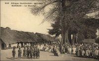 Kankan, le marché. (en 1905). – « Arrivée à la gare de Kankan peu avant midi. Les chefs indigènes, dont un descendant de Samory, viennent nous voir à la gare, drapés, la tête enveloppée de linges blancs, assez semblables à des Flamands du XVème  siècle. Dehors, la milice composée d'anciens tirailleurs, khaki et rouge, porte les armes. Alors éclate, comme une bombe sous le soleil, dans la poussière, avec une brusquerie extraordinaire, mon premier tam-tam d'Afrique »(1). « Jusqu'en 1911 l'orientation soudanienne demeura  prépondérante : les marchandises d'importation arrivaient de Bamako à Kouroussa (terminus des 400 km du bief navigable supérieur du Niger) et à Kankan (par le Milo). La construction du chemin de fer et celle du réseau routier ont renversé l'orientation traditionnelles des courants d'échange au bénéfice de Conakry et donné à Kankan un nouvel essor » (2). Sources : (1) Morand, Paul, A.O.F. de Paris à Tombouctou, Paris, Flammarion, 1928 ; (2) Suret-Canale, Jean, La République de Guinée, Paris, Editions Sociales, 1970. - Cette carte fait partie du travail du célèbre photographe et éditeur dakarois Edmond Fortier (1862-1928) à qui l'on doit une somme importante de clichés sur toute l'Afrique de l'Ouest. M. Fortier tenait boutique non loin du marché Kermel, à l'angle de la rue Dagorne et du boulevard Pinet-Laprade. Cette photo doit dater de 1905. Edmond Fortier avait effectué un voyage en Guinée en 1902 ou 1903, mais il semble qu'il soit allé à Kankan par le fleuve, comme cela se faisait avant l'arrivée du chemin de fer, depuis Bamako, à l'occasion d'un périple au Soudan français en 1905.