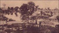 Gaoua, passage du bac de Nabéré (route Gaoua-Bobo).  «Privée de débouchés naturels et de voies ferrées, la Haute-Volta est, par contre, sillonnée d'admirables routes. Beaucoup d'autos la parcourent. Elles assurent la  vie du pays. Le gouvernent en a, pour son compte, une soixantaine, postales et autres; c'est un véritable parc d'armée. Les autos, et non le chemin de fer, ici comme ailleurs, sont l'avenir». Source : Morand, Paul, A.O.F. de Paris à Tombouctou, Paris, Flammarion, 1928.