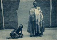 Le Mogho-Naba, Chef de tous les Mossis et un serviteur. Carte éditée par la Mission d'Ouagadougou vers 1920.  – « Hier, à Ouagadougou, j'ai été rendre visite au Moro-Naba, le roi de tout le pays Mossi. Il règne sur deux à trois millions de sujets et ses ancêtres furent en rapport avec les Portugais. M. Delafosse a même pu établir la chronologie des rois Mossi jusqu'à l'an mil. Le roi m'attend sur la porte de son palais, entouré de sa cour. Il est obèse ; une vraie outre noire, grasse ; l'air sensuel, féroce et malin. Barbiche, joues énormes. C'est bien le dernier roi nègre, celui de mes livres d'enfant. Il porte une énorme couronne d'or, une robe de velours violet soutachée d'or, et rafraîchit ses lourdes lèvres violacées d'une petite langue de carmin qui égaye de sa couleur tout le visage. Il me présente ses ministres, ses scribes, ses eunuques, ses pages, très beaux et vêtus de robes, coiffés en cimier, comme des femmes, comme elles guêtrés de jambières de cuivre de vingt centimètres de haut, parés de lourds anneaux de cuivre rose, d'une tonalité merveilleuse sur la peau nue. […] J'offre au Moro-Naba un bracelet d'émeraudes, acheté à Paris dans une de ces boutiques de faux à « tout pour cent francs… » (1). - Il doit s'agir du Mogho Naaba Koom II (1889 – 1942), l'arrière grand-père du Mogho Naaba actuel, qui régna du 27 février 1905 à sa mort, le 12 mars 1942. Il avait choisi pour devise « Que l'eau abonde pour tous ». Il repose, ainsi que sa femme, au centre de la place qui porte son nom devant la gare ferroviaire de Ouagadougou, sous la masse d'une statue métallique de 6 mètres de haut représentant une femme mossi stylisée offrant l'eau de bienvenue à un hôte invisible. Mogho Naaba Koom II s'était rallié à la France Libre dès le 22 juin 1940, alors que Paul Morand, dont on sent percer le dédain dans les lignes que lui a consacrées, sera nommé ambassadeur de France en Roumanie puis en Suisse par Vichy. Source : (1) Morand, Paul, A.O.F. de Paris à Tombouctou, Paris