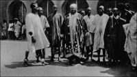 Le Moro-Naba, un des rois de la Haute-Volta, et sa cour. – « Hier, à Ouagadougou, j'ai été rendre visite au Moro-Naba, le roi de tout le pays Mossi. Il règne sur deux à trois millions de sujets et ses ancêtres furent en rapports avec les Portugais. M. Delafosse a même pu établir la chronologie des rois Mossi jusqu'à l'an mil. Le roi m'attend sur la porte de son palais, entouré de sa cour. Il est obèse ; une vraie outre noire, grasse ; l'air sensuel, féroce et malin. Barbiche, joues énormes. C'est bien le dernier roi nègre, celui de mes livres d'enfant. Il porte une énorme couronne d'or, une robe de velours violet soutachée d'or, et rafraîchit ses lourdes lèvres violacées d'une petite langue de carmin qui égaye de sa couleur tout le visage. Il me présente ses ministres, ses scribes, ses eunuques, ses pages, très beaux et vêtus de robes, coiffés en cimier, comme des femmes, comme elles guêtrés de jambières de cuivre de vingt centimètres de haut, parés de lourds anneaux de cuivre rose, d'une tonalité merveilleuse sur la peau nue. […] J'offre au Moro-Naba un bracelet d'émeraudes, acheté à Paris dans une de ces boutiques de faux à « tout pour cent francs… » (1). - Il doit s'agir du Mogho Naaba Koom II (1889 – 1942), l'arrière grand-père du Mogho Naaba actuel, qui régna du 27 février 1905 à sa mort, le 12 mars 1942. Il avait choisi pour devise « Que l'eau abonde pour tous ». Il repose, ainsi que sa femme, au centre de la place qui porte son nom devant la gare ferroviaire de Ouagadougou, sous la masse d'une statue métallique de 6 mètres de haut représentant une femme mossi stylisée offrant l'eau de bienvenue à un hôte invisible. Mogho Naaba Koom II s'était rallié à la France Libre dès le 22 juin 1940, alors que Paul Morand, dont on sent percer le dédain dans les lignes qui lui a consacrées, sera nommé ambassadeur de France en Roumanie puis en Suisse par Vichy. Source : (1) Morand, Paul, A.O.F. de Paris à Tombouctou, Paris, Flammarion, 1928.