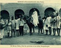 Morom Naba, chef de province et sa suite, Ouagadougou – Carte postale éditée par la Mission de Ouagadougou – Il doit s'agir du Mogho Naaba Koom (1889 – 1942), l'arrière grand-père du Mogho Naaba actuel, un empereur qui avait choisi pour devise «Que l'eau abonde pour tous». Mogho Naaba Koom s'était rallié à la France Libre dès le 22 juin 1940. Il repose, ainsi que sa femme, au centre de la place qui porte son nom, devant la gare ferroviaire de Ouagadougou, sous la masse d'une statue métallique de 6 mètres de haut représentant une femme mossi stylisée offrant l'eau de bienvenue à un hôte invisible.