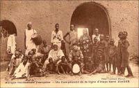 Un campement de la ligne d'étape Kano Zinder. - Distantes de 250 km, les villes de Zinder au Niger et Kano au Nigeria sont des escales importantes d'une voie de communication ancestrale, joignant le Golf de Guinée à l'Afrique du Nord, soit l'Atlantique à la Méditerranée via le Sahara. De longue date, des caravanes l'empruntent pour assurer les échanges entre les régions riches en or et ivoire et la tripolitaine. La conquête coloniale laisse une large partie du trajet dans le giron français, hormis l'extrémité méridionale, sous contrôle britannique. Même si elle est peu utilisée par les colonisateurs, qui préfèrent évoluer dans les limites de leurs propres possessions, elle reste néanmoins sécurisée par leurs soins, pour maintenir le commerce africain, source de revenus imposables. Pour cela, les étapes sont généralement érigées en postes militaires, gardés par une troupe indigène sous le commandement d'un officier ou d'un sous-officier européen. Cette piste n'est que rarement employée pour l'approvisionnement et le courrier des postes français du Niger, de la côte atlantique vers le sahel. Les voies via Say au Dahomey, voire via le Congo et le Tchad, lui sont préférées. Plus tard, après la Seconde Guerre mondiale, la ligne est exploitée par les petits autocars d'une entreprise privée algérienne. La Société des transports tropicaux relie ainsi le Maghreb à l'Afrique de l'Ouest, d'Alger à Kano en passant par Zinder, soit 3945 kilomètres, en 12 jours et 8 nuits d'hôtel passées dans les villes étapes. A Zinder, le voyageur venu d'Algérie pouvait aussi attraper –ou attendre- une correspondance pour Niamey ou Fort-Lamy.