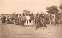 Zinder, le marché. – Le général Gouraud, figure de la conquête coloniale, décrit ainsi Zinder et son marché en avril 1902 - il était alors commandant -, tandis qu'il y rentre pour la première fois : « Zinder est le grand centre de transit de cette partie de l'Afrique centrale. […] Au Nord, à 1500 mètres [de Zinder], se trouve la ville Targuie de Zengou. […] On y rencontre des Tripolitains, quelques Touareg. Elle compte 4 à 5000 habitants. […] Le marché de Zengou est animé. On y trouve en particulier de beaux cuirs, les bottes en filali de toute l'Afrique centrale et que nous portons nous-mêmes, des brides brodées ; les bijoux ne valent pas les délicats filigranes des bijoux soudanais et sénégalais ; il y a de jolies calebasses ouvragées de toutes dimensions, la calebasse pouvant servir d'écuelle aussi bien que de malle aux femmes du pays, qui y empilent leurs étoffes et leurs ustensiles et la portent sur la tête. On y voit des musiciens, des danseuses, aux cadences lentes et balancées, un homme-orchestre. Il y a encore sur le marché de Zengou du sel de Bilma, comme à Tombouctou du sel de Taodénit » (1) – La carte, signée « Photo Combier Mâcon », fait assurément partie de la production de la maison CIM (Combier imprimeurs à Mâcon). Cette entreprise, fondée par Jean Combier avant la première guerre mondiale, éditera quelques 2 millions de carte postales essentiellement consacrées aux régions françaises – colonies comprises – entre 1907 et 1982 (2). Source : (1) Gouraud, Général, Zinder, Tchad - Souvenirs d'un Africain, Paris, Plon, 1944. (2) Combier, Marc, Un siècle de cartes postales, Paris, Alternatives, 2005.