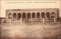 Zinder, Palais du gouverneur (face sud). – Il s'agit apparemment du même bâtiment qui servit, lorsque la région était un territoire militaire – jusqu'en 1922 où elle devint « Colonie du Niger » -, d'habitation au commandant dudit territoire.  Le Général Gouraud, figure de la conquête coloniale,  qui occupa ce poste en 1902 alors qu'il n'était que commandant, décrit les lieux en en ces termes : « Ma maison, que le colonel comparait élégamment à la casbah d'un boy maugrébin du XVè siècle, est un dédale de salles, de cours, de corridors, de réduits, où depuis trois jours je n'arrive pas à me retrouver. Il y a deux pièces meublées richement, tentures de velours, de soie, d'or, etc… ». - La garnison de Zinder compte alors 380 hommes : « une forte compagnie de tirailleurs, un peloton d'auxiliaires et des spahis qui viennent d'arriver. Elle dispose de 2 pièces de canon ». Source : Gouraud, Gal, Zinder Tchad, Paris, Plon, 1944.