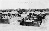 Zinder, vue générale du Berny – Description de Zinder en avril 1902, quand y entre le commandant Gouraud : «La ville est entourée d'un fort rempart à dents de scie en bon état, rappelant celui de Sikasso […] les rues de la ville sont étroites, comme dans toutes les villes soudanaises. Peu de maisons en terre, beaucoup de cases en paille, d'immenses trous, là où on a pris la terre, des amas de blocs de grès arrondi et lavé par les pluies, une des caractéristiques du pays. La ville est sale, les vautours et les chiens étant seuls chargés de la voirie. Beaucoup de beaux arbres dans la ville et aux environs. […] Zinder est le grand centre de transit de cette partie de l'Afrique centrale. […] Au Nord, à 1500 mètres [de Zinder], se trouve la ville Targuie de Zengou. […] On y rencontre des Tripolitains, quelques Touareg. Elle compte 4 à 5000 habitants. […] Le marché de Zengou est animé. On y trouve en particulier de beaux cuirs, les bottes en filali de toute l'Afrique centrale et que nous portons nous-mêmes, des brides brodées ; les bijoux ne valent pas les délicats filigranes des bijoux soudanais et sénégalais ; il y a de jolies calebasses ouvragées de toutes dimensions, la calebasse pouvant servir d'écuelle aussi bien que de malle aux femmes du pays, qui y empilent leurs étoffes et leurs ustensiles et la portent sur la tête. On y voit des musiciens, des danseuses, aux cadences lentes et balancées, un homme-orchestre. Il y a encore sur le marché de Zengou du sel de Bilma, comme à Tombouctou du sel de Taodénit ». Source : Gouraud, Général, Zinder, Tchad - Souvenirs d'un Africain, Paris, Plon, 1944.