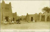 Zinder, maisons de commerçants tripolitains. – Description de Zinder en avril 1902, quand y entre le commandant Gouraud : « Zinder est le grand centre de transit de cette partie de l'Afrique centrale. […] Au Nord, à 1500 mètres [de Zinder], se trouve la ville Targuie de Zengou. […] On y rencontre des Tripolitains, quelques Touareg. Elle compte 4 à 5000 habitants. […] Le marché de Zengou est animé. On y trouve en particulier de beaux cuirs,  les bottes en filali de toute l'Afrique centrale et que nous portons nous-mêmes, des brides brodées ; les bijoux ne valent pas les délicats filigranes des bijoux soudanais et sénégalais ; il y a de jolies calebasses ouvragées de toutes dimensions, la calebasse pouvant servir d'écuelle aussi bien que de malle aux femmes du pays, qui y empilent leurs étoffes et leurs ustensiles et la portent sur la tête. On y voit des musiciens, des danseuses, aux cadences lentes et balancées, un homme-orchestre. Il y a encore sur le marché de Zengou du sel de Bilma, comme à Tombouctou du sel de Taodénit ». Source : Gouraud, Général, Zinder, Tchad - Souvenirs d'un Africain, Paris, Plon, 1944.