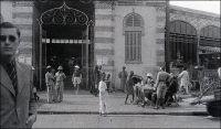 Dakar, devant le marché européen, janvier 1941. Photo d'amateur, légende manuscrite. – Il s'agit, bien sûr, du marché Kermel. L'époque – début 1941 - est un peu particulière, puisque Dakar est alors la capitale vichyste de l'Afrique noire. Elle vient de repousser, quelques mois auparavant, une tentative de débarquement des forces de la France libre – dirigées par De Gaulle lui-même - et de la marine britannique, les 23 et 24 septembre 1940. La farouche opposition dakaroise tient pour partie à la défiance de la marine française envers les Anglais, qui venaient de mener une attaque très destructrice et meurtrière contre la flotte nationale dans le port algérien de Mers-el-Kébir. Elle tient aussi à la personnalité du gouverneur-général Pierre Boisson, nommé deux mois plus tôt à la tête de l'AOF et de l'AEF par Vichy (alors même que l'AEF, qu'il gouvernait jusque là, avait formellement rallié le gaullisme au lendemain de son départ de Brazzaville pour Dakar). Il resta encore fidèle à Pétain  jusqu'au 22 novembre 1942, deux semaines après le débarquement des troupes américaines au Maroc et alors que la plupart des colonies vichystes avaient rejoint le camp des alliés. Signe de sa détermination antigaulliste, il négocie son ralliement à Darlan – le chef de l'armée française d'Afrique qui vient de passer dans le camp des alliés – en excluant toute ingérence gaulliste sur le territoire. Durant les tractations, le 19 novembre 1942, le résistant Adolphe Gaétan fut même fusillé à Dakar, pour « menées gaullistes ». Pierre Boisson sera remplacé en novembre 1943, poursuivi et révoqué par le tribunal d'Alger durant la guerre puis condamné par la Haute cour de justice en 1948, peu avant sa mort. La bataille de Dakar, en septembre 1940, fit de gros dégâts et de nombreuses victimes civiles dans la ville. Elle se solda par un fiasco militaire pour les assaillants, et par un cuisant revers politique pour De Gaulle et Churchill, qui faillit alors être démissionné.