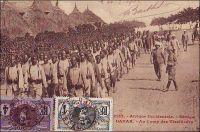 Dakar, au camp des tirailleurs. - 212 000 Africains, de toute l'AOF, prirent part en tant que tirailleurs sénégalais aux hostilités de la Grande guerre, dont 165 000 sur le sol métropolitain. 30 000 furent tués. Le corps des tirailleurs sénégalais avait été créé en 1857 par Louis Faidherbe, alors gouverneur général de l'AOF, pour palier, en cette époque de conquête coloniale, le déficit de troupes venant de Métropole. Initialement composée d'esclaves rachetés à leurs maîtres africains et affranchis, et de volontaires issus des élites locales, les régiments de tirailleurs sénégalais s'apparentent à des troupes mercenaires. Mais la mobilisation de tous les Africains de plus de 18 ans décidée en 1915, et l'engagement pour défendre la Nation vont en faire un corps d'engagés et de conscrits des plus légitimes. 17 régiments de tirailleurs sénégalais participent à la bataille de la Somme, subissant d'importantes pertes qui vaudront au Général Mangin, par ailleurs promoteur des troupes africaines, le surnom de « boucher des noirs ». - Cette carte postale fait partie du travail du célèbre photographe et éditeur dakarois Edmond Fortier (1862-1928) à qui l'on doit une somme importante de clichés sur l'Afrique de l'Ouest en général et sur le Sénégal en particulier ; il a publié en tout 3300 clichés originaux. M. Fortier tenait boutique et vivait avec ses deux filles blondes et son boy Seydou Traoré, à l'angle de la rue Dagorne et du boulevard Pinet-Laprade.