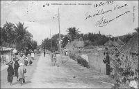 Saint-Louis, route de Sor. – L'île de Sor, située en face de l'île portant le centre ville de Saint-Louis, commence à se développer au XIXème siècle, à mesure que ses marécages sont assainis. Son aménagement, pour en faire une ville jumelle de Saint-Louis sous le nom de Saint-Philippe, avait été envisagé dès 1837 par le ministre de la Marine et des colonies de Louis-Philippe. Le projet, qui avait fait long feu, est relancé en 1852, et l'on baptise alors le nouveau quartier, implanté au nord de la vaste île, Bouetville en référence au gouverneur Bouet-Willaumet (1843-1845). Mais le lieu, isolé du centre par le grand bras du fleuve Sénégal, n'attire pas encore beaucoup d'habitants ; il n'en compte que 308 en 1857. La mise en place d'un bac régulier en 1858, puis d'un pont en 1865 par Faidherbe, facilite l'implantation humaine. L'arrivée du chemin de fer en 1885, dont l'ensemble des installations saint-louisiennes est déployé à Sor, va contribuer au développement du sud de l'île, baptisé Léona. Progressivement, les quartiers et les sous quartiers de Sor se structurent et se peuplent, dans un environnement luxuriant de cocotiers, de filaos et de prosopis verts. Au moment où le Sénégal accède à l'indépendance, en 1960, Sor compte 24 352 habitants.– Cette photo fait partie du travail du célèbre photographe et éditeur dakarois Edmond Fortier (1862-1928) à qui l'on doit une somme importante de clichés sur l'Afrique de l'Ouest en général et sur le Sénégal en particulier ; il a publié en tout 3300 clichés originaux. M. Fortier tenait boutique et vivait avec ses deux filles blondes et son boy Seydou Traoré, à l'angle de la rue Dagorne et du boulevard Pinet-Laprade.