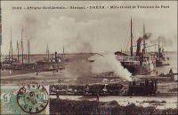 Dakar, Môle ouest et travaux du port – La ville de Dakar, devenue en 1902 la capitale de l'AOF, reçoit dès lors de forts investissements publics, pour développer les infrastructures tant civiles que militaires. Progressivement, le port qui est desservi par le chemin de fer à partir de1883, s'impose devant les autres installations du pays, et notamment Rufisque et Saint Louis. La machine à la manœuvre est la locomotive n°2 de type 030 T, fabriquée par les ateliers des Batignolles à Paris en 1883. – Cette photo fait partie du travail du célèbre photographe et éditeur dakarois Edmond Fortier (1862-1928) à qui l'on doit une somme importante de clichés sur l'Afrique de l'Ouest en général et sur le Sénégal en particulier ; il a publié en tout 3300 clichés originaux. M. Fortier tenait boutique et vivait avec ses deux filles blondes et son boy Seydou Traoré, à l'angle de la rue Dagorne et du boulevard Pinet-Laprade.
