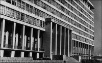 Dakar, le building administratif du G. G. – Construit en 1953, sur les plans de M Cerutti-Maori, architecte en chef de l'AOF, cet immeuble, qui a 120 m de façade et dix étages de hauteur abrite les services du Gouvernement Général de l'AOF. La vue sur la presqu'île du Cap Vert et l'île de Gorée, depuis sa terrasse supérieure, est réputée. Cet imposant édifice est représentatif d'une époque où l'on introduit dans les capitales coloniales des techniques de construction basées sur le béton, techniques jusqu'alors réservées aux métropoles occidentales. Les nouveaux bâtiments, principalement concentrés dans la partie européenne des villes et s'élevant à de grandes hauteurs, renforcent le contraste architectural avec les quartiers indigènes où prédominent les constructions basses. Pendant un temps, ces immeubles vont se distinguer de leurs équivalents européens par l'adjonction sur les façades de pare-soleil et d'ouvertures en claustra, évitant la climatisation de tous les espaces intérieurs ; c'est le cas du building administratif de Dakar. Puis, la réduction du coût de l'énergie dans les années soixante, poussant à la généralisation du « tout climatisé », va entraîner la disparition de ces derniers signes spécifiques d'une architecture tropicale.