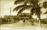 Saint-Louis, l'avenue de la Gare. – Le bâtiment que l'on aperçoit au fond est la première gare de Saint-Louis. On l'appelait le « Bâtiment des voyageurs », elle fut inaugurée avec la ligne Dakar-Saint-Louis le 6 juillet 1885, et se situait sur l'emplacement des Travaux Publics dans le quartier de Léona à Sor. Ces terrains marécageux avaient été progressivement viabilisés dans la seconde moitié du XYX ème siècle. La voie ferrée se prolongeait au-delà de la gare, en bordure d'un marigot, jusqu'à la gare marine dont la jetée était sur la rive gauche. Le budget important alloué à sa construction, 150 000 francs, devait susciter quelques années plus tard la jalousie des  habitants de Conakry, qui n'eurent droit qu'à un édifice plus simple comme terminal de la ligne Conakry-Niger. L'ancienne gare de Saint-Louis fut remplacée dès 1909 par la gare actuelle, laquelle a été édifiée sur le site du premier cimetière de Sor.