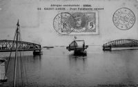 Saint-Louis, pont Faidherbe ouvert – Inauguré par deux fois, le 14 juillet 1897 par le gouverneur-général Chaudié et le 19 octobre de la même année par André Lebon, premier ministre des Colonies à se rendre au Sénégal, il remplace le pont flottant du même nom. Ce dernier avait été inauguré le 2 juillet 1865 par le colonel du Génie Pinet-Laprade, en remplacement du bac de Rouet ville, lui-même inauguré le 10 juin 1858 et qui permettait l'emport de 150 passagers par voyage pour 10 rotations par jour, ce qui s'avéra très vite insuffisant. Le pont flottant, composé de 40 pontons flottants en tôle de 4 t chacun, et d'un tablier de bois de 4 m de large, possédait une portière de trois pontons qui permettait un passage de 20 mètres pour les navires. La délicate manœuvre d'ouverture avait lieu une fois par jour. Ce pont, qui faisait au total 680 m avec une partie flottante de 355 m, nécessitait un entretien intensif et coûteux, mobilisant une équipe de 16 personnes pour vider quotidiennement l'eau infiltrée dans les pontons, vérifier les amarres… Il resta néanmoins en service 32 ans durant.