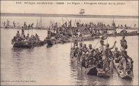 Le Niger, pirogues [au] retour de la pêche. - Jusqu'à la fin du XVIIIème siècle, les Européens se firent une idée erronée du Niger dont l'existence était mentionnée depuis l'antiquité par Pline l'Ancien (23-79). La plupart de leurs connaissances géographiques sur le continent africain reposaient, il est vrai, sur les écrits d'auteurs arabes dont le géographe Idrissi (XIIème siècle), qui n'avait jamais mis les pieds en Afrique, et le voyageur Léon l'Africain (XVIème siècle), qui décrivait plus de choses qu'il n'avait pu en voir. De fait, les occidentaux pensèrent longtemps que le fleuve prenait sa source dans le lac du Bornou, actuel Tchad, et courait vers l'ouest. Ils croyaient également qu'il aboutissait dans l'Atlantique par un immense delta pourvu de quatre branches, le Sénégal, la Gambie, le Rio Gacheo et le Rio Grande… Il fallut attendre le géographe français d'Anville, en 1749, pour imaginer que le fleuve Sénégal et le Niger étaient deux cours d'eau distincts et que le second coulait vers l'est. Et c'est l'explorateur écossais Mungo Park qui le vérifia sur le terrain en 1796, vers Ségou dans l'actuel Mali. Plus tard, la lutte pour le contrôle de cette voie navigable de l'intérieur du continent opposa colonisateurs français et britanniques. Les premiers parvinrent à tenir les sources, le delta central soudanien et le cours moyen mais se firent finalement ravir le cours inférieur par les seconds. Pour les occupants ancestraux de ces régions, le Niger est tout à la fois une véritable mer intérieure poissonneuse, un formidable couloir de communication et de commerce et la source de l'eau et du limon propices à une vaste zone fertile aux frontières du désert. - Cette carte postale fait partie du travail d'Edmond Fortier (1862-1928), photographe et éditeur établi à Dakar. Elle doit dater de fin 1905, époque à laquelle il fit un voyage au Soudan.