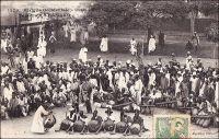 Tam-tam à Bamako. – « Deux jours de repos à Bamako, tandis que nous organisons la caravane qui doit nous emmener vert Tombouctou. […] Ce soir, encore un tam-tam : groupe d'une centaine de danseurs et d'un nombre à peu près égal de figurants. C'est une belle mascarade. Le chef des griots porte un peplum bleu-noir et est coiffé d'un casque doré de lancier Second Empire, à cimier de crin. Les vieilles femmes, comme toujours, sont  déchainées ; elles portent les couleurs les plus voyantes et ne le cèdent à personne en lascivité. La grande vedette remue furieusement le derrière ; un homme se détache du groupe, et pour mettre ce spectacle en valeur, pose une main au bon endroit ; on voit ses doigts noirs se détacher sur la jupe blanche de la danseuse. Pendant ce temps les tambours lâchent des pétarades d'obusiers qui font trembler le palais. Les femmes poussent des cris de tête, les balafons de bois sonore laissent couler des gammes sur leurs deux octaves, et les clochettes de fer attachées aux chevilles font un bruit de rideau métallique. Les acteurs se passent un seau de zinc plein d'eau, à même lequel ils boivent, sans interrompre leur action. Ils s'avancent et profèrent d'un air féroce des paroles hurlées, qu'on nous affirme encore être nos louanges et celles des parents qui nous ont conçus ; les chefs commentent cette récitation héroïque par des exclamations parlées qui en soulignent le sens, comme les méthodistes américains accompagnent d'aboiements les discours de leur ministre ; c'est tout à fait le shouting des nègres baptistes. Le proverbe guinéen dit : Les griots chantent seulement les louanges des vivants » (1). Cette carte postale fait partie du travail d'Edmond Fortier (1862-1928), photographe et éditeur établis à Dakar. Elle doit dater de fin 1905, époque à laquelle il fit un voyage au Soudan.  Sources : (1) Morand, Paul, A.O.F. de Paris à Tombouctou, Paris, Flammarion, 1928.