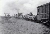 Chemin de fer de Kayes au Niger, voyageurs de 4ème classe. - « Nous partons le 10  [février 1901, de Bamako vers Kayes] par le chemin de fer, occupant le dernier wagon, avec une sorte de balcon d'où je peux retrouver tous les souvenirs épars de ce paysage : c'est la neuvième fois que je fais cette route. » (1). – Assez tôt, les autorités coloniales envisagent de relier, par un chemin de fer, le fleuve Sénégal, principale voie de pénétration dans cette partie du continent, au fleuve Niger, voie essentielle de circulation dans le Sahel. Les premières études ont lieu en 1880, alors même que toute la région n'est pas sous contrôle français. La ligne devra aller de Kayes, sur le fleuve Sénégal, jusqu'à Koulikoro, sur le Niger, et les travaux débutent dès 1881, mais au ralenti tant la main d'œuvre locale et l'encadrement européen sont défaillants. L'avancée est très lente, et en 1884, seuls 53 km ont été couverts alors que l'entreprise a d'ores et déjà englouti des sommes exorbitantes ; la construction sera finalement confiée au Génie militaire. Le premier tronçon, allant de Kayes à Bafoulabé est inauguré le 1er janvier 1894. La construction du reste de la ligne, joignant le fleuve Niger, durera encore jusqu'en 1904, et nécessitera des efforts importants, comme l'édification d'un viaduc de 400 mètres à Mahina. Ce réseau est connecté en 1924 à celui du Sénégal, permettant le transport sans rupture de charge du port maritime de Dakar au port fluvial de Bamako. Sources : (1) Gouraud, Général, Zinder, Tchad - Souvenirs d'un Africain, Paris, Plon, 1944.