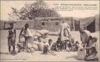 Boucle du Niger. Comptage des Kauris dans un poste. Les Kauris sont de petits coquillages servant de monnaie au Soudan (valeur moyenne, 1 franc le mille). – Le Soudan est, avec le Dahomey, le dernier territoire où le colonisateur français autorisa le paiement des impôts en coquillages, jusqu'en 1907. La parité qui avait longtemps fluctué dans les colonies françaises autour de 1000 coquillages pour 1 franc, s'établissait alors à 20 000 cauris pour 7 francs. Par la suite, les lois devaient interdire l'emploi monétaire des coquillages. Ils restèrent néanmoins tardivement utilisés pour des transactions locales informelles. Ainsi on estimait à 70 000 cauris la dot due à la famille d'une épouse, au Niger à la fin des années 1940. Les Kauris ou cauris auraient été introduits en Afrique noire entre le IXème et Xème siècle par le biais du commerce arabe transsaharien. Ces coquillages des mers chaudes étaient utilisés comme monnaie dans les îles du continent indien depuis 3000 ans avant JC. Les échanges avec les navigateurs portugais et espagnols, et notamment  la traite négrière, ont contribué à les diffuser largement sur le continent noir.  Dans la seule décennie qui va de 1850 à 1860, 35 000 tonnes de cauris auraient été importées en Afrique pour acquérir de l'huile de palme et des esclaves. Les types de coquillage et leur parité marchande varièrent selon les régions et les époques. Outre les cauris (Cypraea annulus, Cypraea moneta, Cypraea caurica, Cypraea onyx, Cypraea argus et Cypraea eglantina), les marginelles (Marginella persicula et Marginella cingulata) eurent cours au Soudan et les olives (Olivella nana) au Congo. - Cette carte postale fait partie du travail du célèbre photographe et éditeur dakarois Edmond Fortier (1862-1928), à qui l'on doit une somme importante de clichés sur l'Afrique de l'Ouest en général ; il a publié en tout 3300 clichés originaux. M. Fortier tenait boutique et vivait avec ses deux filles blondes et son boy Seydou Traoré, à l'angle de la ru