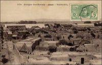 Bamako, vue générale. – « Ils sont plus de vingt mille Soudanais à Bamako. La France a construit là une grande ville indigène, ville de banko, c'est-à-dire en boue. Aucune case ne dépasse l'autre. Cela s'étend comme un cimetière où l'on aurait enterré que des pauvres ; un cimetière de la zone des armées, égalitaire. Au-dessus des murs entourant ces cases, on voir monter et descendre en cadence l'instrument symbolique de l'Afrique entière : le long bâton à piler le mil ». Source : Londres, Albert, Terre d'ébène, Paris, Albin Michel, 1929.