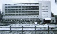 Lomé, l'hôtel Le Bénin en cours d'achèvement. –Premier établissement aux normes modernes d'Afrique de l'Ouest, il est bâti en un temps record, pour être achevé le 27 avril 1960, date de la proclamation d'indépendance. Il devait en effet héberger les personnalités étrangères invitées à la cérémonie. Sylvanus Olympio, le premier président, souvent considéré comme l'artisan de cette nouvelle souveraineté, ne devait pas achever son mandat. Il est assassiné le 13 janvier 1963, vraisemblablement à l'instigation de la France. Paris et son « monsieur Afrique » d'alors, Jacques Foccart, n'auraient pas supporté la volonté d'émancipation du chef d'Etat togolais. Celui-ci venait d'annoncer sa sortie prochaine de la zone CFA, au profit d'une monnaie qu'il souhaitait voir adossée au mark allemand. Réveillé dans la nuit par l'intrusion de militaires à son domicile, il s'était réfugié dans le parking de l'ambassade américaine voisine. Mais il est livré à ses bourreaux par l'ambassadeur lui-même, qui l'avait pourtant assuré de sa protection en le découvrant caché dans une voiture. Selon les témoignages, les aveux et les époques, son exécution a été attribuée à trois hommes distincts : le sergent chef Etienne Gnassingbé, qui finira par prendre le pouvoir en 1967 sous le nom de Gnassingbé Eyadéma, un autre sous-officier togolais nommé Robert Adéwi, de sinistre  mémoire, et le commandant français Georges Maitrier. Le fils de Sylvanus Olympio devait longtemps porter le flambeau de l'opposition, avant de se rallier récemment au pouvoir, occupé depuis la mort du général Eyadéma par un de ses fils. La fête nationale du Togo, fixée au 13 janvier du temps du président Eyadéma, commémore ainsi à la fois la date d'un assassinat et celle du premier coup d'Etat sanglant de l'Afrique indépendante. – Cette photo provient du fonds de Léon Anselmo, qui vécut au Togo et prit part à la construction de nombreux édifices dont l'hôtel Le Bénin.