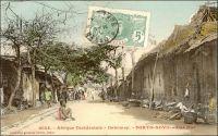 Porto-Novo, une rue. – « Porto-Novo et la banlieue d'Hogbonou nous offrent des types d'habitations retrouvés nulle part ailleurs. Rien n'est plus curieux que de pérégriner le long des ruelles étroites, creusées de ravines, coupées de ponts fragiles. Nous voyons des maisons dont la terre de barre est dissimulée sous un revêtement de couleur bleu pâle, ocre jaune, rouge, garnies de mirador, de faux balconnets, de croisillons aux fenêtres, vestiges des premiers Portugais qui vinrent sur cette Côte des Esclaves, vers le XVIè siècle » (1). Cette carte postale fait partie du travail du photographe et éditeur dakarois Edmond Fortier (1862-1928). Elle appartient à un reportage qu'il mena dans le sud du Dahomey en 1908, alors qu'il accompagnait, depuis l'escale de Dakar, le voyage officiel accompli sur la côte oust africaine par le Ministre des colonies Raphaël Milliès-Lacroix. Sources : (1) Bonzon, L., Despois, J., Lacharriere de, L., Leyritz, A., Marquis-Sebie, D., Multedo de, C., Rectenwald G. et Reste, J.F., Le domaine colonial français, Paris, éditions du Cygne, 1929.