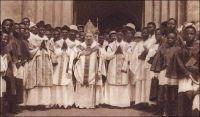 L'église en marche : une ordination à Ouidah. Carte postale des Missions Africaines de Lyon. – L'évangélisation du Dahomey, dans la deuxième moitié du XIXème siècle, est une gageure pour les missionnaires catholiques. Ils considèrent en effet cette contrée comme particulièrement sauvage en raison de la persistance des sacrifices humains. « L'auréole de barbarie qui couronnait si lugubrement le nom du Dahomey exerçait une sorte de fascination », raconte Valérien Groffier (1), secrétaire général de l'œuvre de la propagation de la foi à Lyon, pour expliquer l'insistance des hommes d'église à s'y rendre. Le récit des hécatombes, accompagnant les funérailles du roi Ghézo en 1858 et la « fête des Coutumes » à Abomey en 1860 – rapporté par M. Lartigues agent local des factoreries Régis de Marseille-, qui auraient coûté la vie à 3000 personnes chacune, décidèrent Rome à envoyer les pères des Missions Africaines de Lyon. Le pape Pie IX accepta le projet en 1860 et les premiers missionnaires débarquèrent à Ouidah en avril 1861. Usant de symbolique, son successeur, Benoit XVI, a choisi cette ville pour lancer cent cinquante ans plus tard un appel à l'Afrique. C'est la troisième visite pontificale dans le pays –Jean-Paul II y est venu en 1982 et 1993- et cela marque l'importance croissante du continent noir dans l'église contemporaine. Les ordres missionnaires comptent souvent de nos jours plus de membres originaires d'Afrique que d'Europe. Et l'avenir démographique de cette religion semble devoir, pour partie, se jouer au sud du Sahara. Sources : (1) Groffier, V., Héros trop oubliés de notre épopée coloniale, Lyon-Paris, Librairie catholique Emmanuel Vitte, 1928.