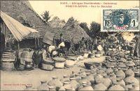 Porto-Novo, sur le marché. - « Le voyageur qui visite pour la première fois Porto-Novo est intéressé par le spectacle des rues. Celles-ci sont en effet très animées : on ne rencontre que femmes portant des caisses de genièvre, de muscat, manœuvres roulant des tonneaux de tafia, indigènes se rendant aux factoreries avec leurs pots d'huile de palme ou avec leur sac d'amande. Les marchandes à la criée ne sont pas inconnues. Chacun peut acheter, dans la rue, la nourriture habituelle de l'indigène : poisson fumé et bouteille d'acaça (farine de maïs bouillie). Dans les cuisines établies en plein vent, on vend au passant des friandises qui sortent toutes chaudes de l'huile de palme bouillante… » (1). Cette carte postale fait partie du travail du photographe et éditeur dakarois Edmond Fortier (1862-1928). Elle appartient à un reportage qu'il mena dans le sud du Dahomey en 1908, alors qu'il accompagnait, depuis l'escale de Dakar, le voyage officiel accompli sur la côte oust africaine par le Ministre des colonies Raphaël Milliès-Lacroix. Sources : (1)Hagen, A, « La colonie de Porto-Novo et le roi Toffa » dans, Revue d'ethnographie [ dir. Hamy, Ernest], Paris, éd. Ernest Leroux, 1887.