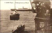Lomé, embarquement au wharf. – L'épreuve du « panier », suspendu à une grue du wharf, est l'étape obligée à Lomé, pour monter à bord des navires ou descendre à terre. Le journaliste Jean Martet, qui fit un voyage au Togo et au Cameroun au début des années 1930, décrit ainsi l'aventure : « Le supplice du panier commence. […] J'ai pris place dans le panier. Le panier n'est naturellement pas un panier. Le panier est une espèce de caisse en bois, sans couvercle ; on dirait un peu une de ces balancelles comme il y en a dans les manèges de chevaux de bois. Seulement dans les manèges de chevaux de bois c'est habituellement peint en rouge, avec des dessins d'or. Ici c'est peint en gris, comme les torpilleurs. De plus, c'est muni par en dessus d'une armature de fer : les anses de ce panier. Je suis donc monté là-dedans […] Je me suis assis sur l'une des deux banquettes dont la balancelle est garni […] J'ai dit à Bernard : On n'aurait donc pas pu trouver quelque chose de plus pratique ? Ça ? m'a-t-il répondu. Qu'est-ce que vous voulez de plus pratique ?   ». Sources :  Martet, Jean, Les bâtisseurs de royaumes, Paris, Albin Michel, 1934.