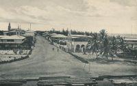 Lomé, Hamburgerstrasse, vers 1908. – La rue du commerce, alors appelée Hamburgerstrasse, est le centre d'affaire historique de la capitale togolaise. La ville s'est d'ailleurs constituée autour de sa vocation commerciale, à partir des années 1870 : des marchands Ewé, installés sur la côte pour mener la traite légitime (l'huile de palme essentiellement) avec les navires européens, sont venus se fixer en bordure de la frontière est de la Gold Coast, pour échapper aux lourdes taxes douanières britanniques. Aux pionniers se sont bientôt joints des commerçants mina venus de l'est et haoussa descendus du nord. Au début des années 1880, des compagnies européennes, allemandes notamment, s'installent à Lomé, alors appelée Bey Beach. C'est sur l'initiative des commerçants allemands de Lomé – qui se sentaient légitimement menacés par les autorités  coloniales anglaises, elles-mêmes exaspérées par cette concurrence à leurs portes - que l'explorateur Nachtigal s'arrête là, signe un traité et proclame le protectorat de l'empire allemand sur le Togo en 1884. - On distingue, sur ce cliché pris depuis la douane allemande – démolie en 1983, pour laisser place à un centre commercial moderne comptant des salles de cinéma, un casino, une boite de nuit et un hôtel -, le siège local des principaux acteurs économiques de la place. Au premier plan à gauche, se trouve la librairie évangélique (bâtie en 1902), suivie juste derrière l'hôtel Vogt, puis moins visible la firme Bödecker-&-Meyer et l'hôtel Kauserhof et enfin dans le fond la cathédrale (1901). En face, de l'autre côté de la rue, on voit l'imposant bureau de l'armateur Woermann, suivie de plusieurs factoreries édifiées entre 1898 et 1903.