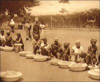 Lomé, vendeuses au marché, (vers 1925). – Dès l'époque coloniale allemande, les revendeuses, éléments caractéristiques du commerce de détail au Togo, commencent leurs fructueuses pratiques, aux côtés de grandes maisons de commerce comme Deusche Togo Geselischaft, Boedecker et Mayer, J. K. Victor, Goedel, et de quelques marchands syriens. Des fortunes accumulées sur la base de petits commerces feront, de quelques togolaises particulièrement avisées en affaires, des « Mama-benz », figures éclatantes de la réussite économique.