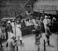 Arrivée du gouverneur du Togo prisonnier à Porto Novo, en 1914. – Il s'agit du commandant Von Doering, qui assurait l'intérim du duc de Mecklemburg en congé lorsque la Grande Guerre éclata. Les parties en présence n'imaginaient pas que le conflit puisse se porter dans la région. Von Doering, avait d'ailleurs vainement proposé à deux reprises par télégramme des 4 et 5 août 1914,  aux gouverneurs du Dahomey, de Gold Coast et d'AOF, de neutraliser son territoire « pour ne pas donner aux Africains le spectacle de guerres entre Européens ». Von Doering, qui ne disposait que d'une force de police insuffisante pour résister à la coalition des troupes britanniques de Gold Coast et françaises du Dahomey (lesquelles se trouvaient alors ponctuellement renforcées par un bataillon venu de Dakar pour soumettre la turbulente peuplade des Holi), organisa la défense du seul site stratégique pour l'Allemagne, la station de radio transmission de Kamina proche d'Atakpamé. Défait après une vaillante résistance, il tente de négocier la reddition 25 août, non sans avoir détruit les installations de Kamina la nuit précédente. Sa reddition, sans qu'aucune condition n'ait été consentie par les vainqueurs, est effective le 26 août. Les prisonniers allemands sont internés au Dahomey, et la presse germanique mène en février 1915 une campagne pour dénoncer leurs conditions de détention. En fait, il se serait s'agit d'une action de propagande, destinée à justifier les mesures prises à l'égard des prisonniers français du camp de représailles d'Ahlen Falkehberger, en Allemagne.