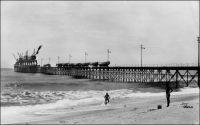 Lomé, le wharf. – Il s'agit du wharf français, bâti en 1928 pour se substituer au wharf allemand de 1904. Le nouvel édifice est construit perpendiculairement à la houle, et non plus à la plage, et possède une structure faite de légers croisillons métalliques offrant peu de résistance aux vagues. Ces précautions n'étaient pas superflues, sachant que le wharf allemand avait été partiellement emporté par la violence de la barre un jour de tempête en 1911. En 1954 le wharf est allongé de 50 m. et le nombre de ses grues porté de 6 à 10 ; la prise de vue est donc antérieure à cette adjonction. En 1962 le président Sylvanus Olympio procède à la pose de la première pierre du port en eau profonde de Lomé, appelé à remplacer le wharf. L'Imposante installation, qui entre en service en 1968, aura un impact environnemental conséquent, contribuant à l'ensablement de la côte occidentale et à l'érosion de la côte orientale.